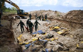 Indonesian soldiers bury quake victims in a mass grave in Poboya after an earthquake and tsunami hit the area on 28 September.