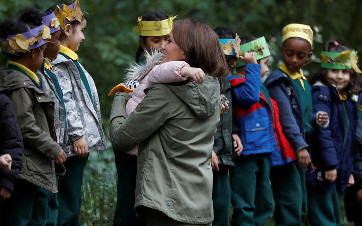 Britain's Catherine, Duchess of Cambridge (R), receives a hug from four-year-old Amwaar, as she says goodbye to school children after visiting to Sayers Croft Forest School and Wildlife Garden in London.