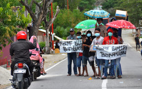 A group of villagers hold placards along a road near their destroyed village, asking for assistance in Palu, Indonesia's Central Sulawesi.