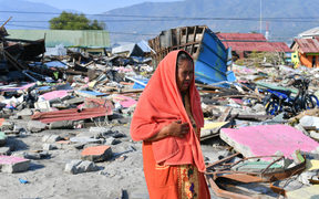 Quake survivor Nurhayati walks at an area where her house once stood in Lere subdistrict in Palu, Indonesia's Central Sulawesi.