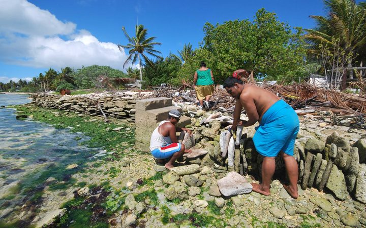 People of Kiritimati coral atoll building a stone seawall to struggle against sea level rise cause by global warming.