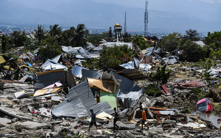 Residents walk past destroyed buildings in the Perumnas Balaroa village in Palu after an earthquake and tsunami hit the area