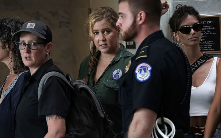 Comedian Amy Schumer waits to be led away after being arrested during a protest against the confirmation of Supreme Court nominee Judge Brett Kavanaugh