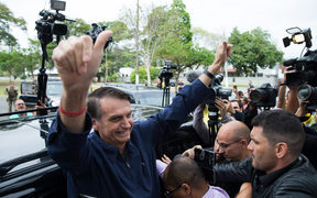 Brazil's right-wing presidential candidate for the Social Liberal Party (PSL) Jair Bolsonaro gives his thumbs up after casting his vote at Villa Militar, during general elections.