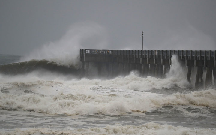 Waves crash along a pier as the outerbands of hurricane Michael arrive in Panama City Beach Florida