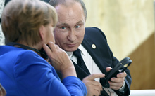 Russian President Vladimir Putin speaks with German Chancellor Angela Merkel during the first day of the COP21 climate change meeting in Paris.