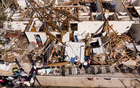 A man works though the remains of an apartment in the aftermath of Hurricane Michael.