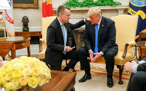 Freed American pastor Andrew Brunson (L) prays for US President Donald Trump at the White House in Washington.