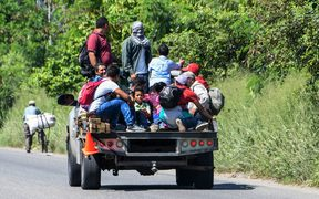 Hondurans get on vans and trucks during the exodus towards the US from San Pedro Sula