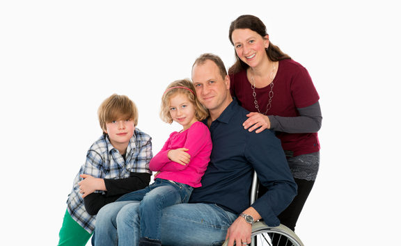 A photo of a disabled man in wheelchair with his family in front of white background