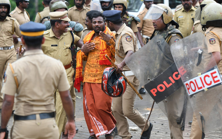 Indian police take a Hindu activist into custody as protesters rallied against a Supreme Court verdict revoking a ban on women's entry to a Hindu temple, in Nilackal in southern Kerala state.