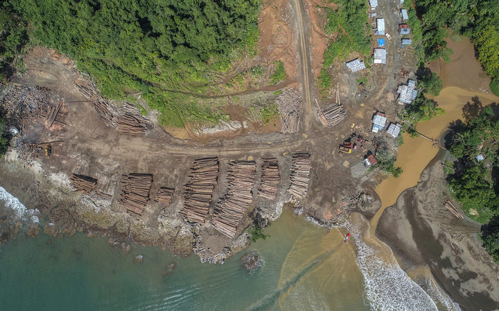 Aerial photo of the coast of the Solomon Islands showing a log landing area with lots of piles of logs waiting to be picked up by boat, plus some logging machinery and huts