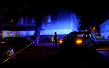 A police officer stands guard during an investigation of a suspicious vehicle on 2 December in Redlands, California.