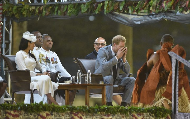 Prince Harry drinks kava as his wife Meghan, the Duchess of Sussex, looks on at a traditional welcome ceremony after they arrived in Suva, Fiji.