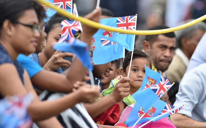 People wave British and Fijian flags as they wait for Britain's Prince Harry and his wife Meghan, the Duchess of Sussex, to arrive for a traditional welcome ceremony.