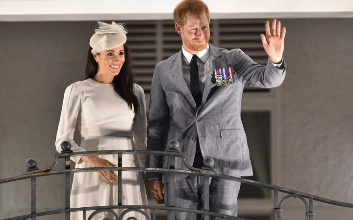 Britain's Prince Harry and and his wife Meghan, the Duchess of Sussex wave from the balcony of the Grand Pacific Hotel in Suva, Fiji.
