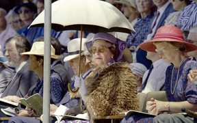 British Queen Elizabeth II (C), shielding herself from the sun with an umbrella, listen to a speech by Anglican Archbishop Hui Vercoe during the celebrations of New Zealand's 150th anniversary in Waitangi on February 6, 1990.