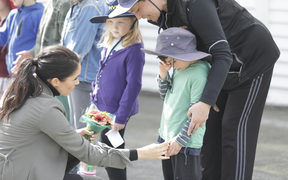 Meghan comforts a young boy who was waiting to catch a glimpse of the royal pair outside Maranui Cafe.
