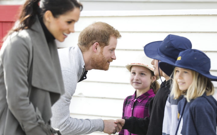Prince Harry and Meghan talk to some schoolchildren outside the Maranui Cafe.
