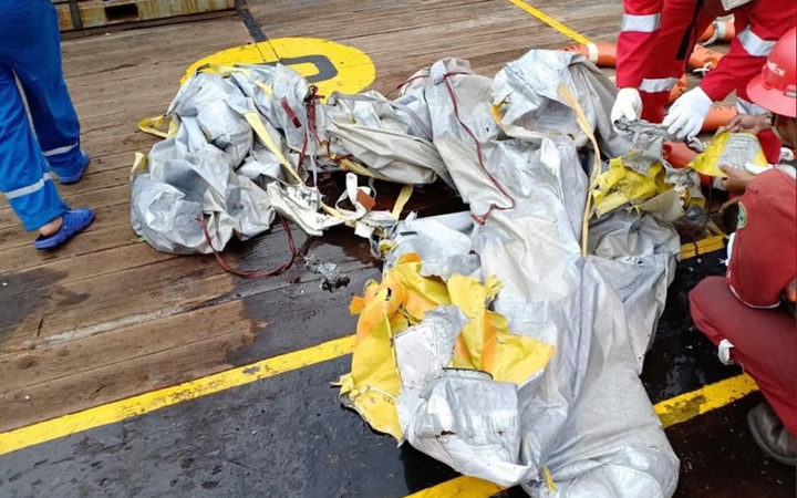 Personnel looking at items believed to be from the wreckage of the Lion Air flight JT 610, recovered off the coast of Indonesia's Java island after the Boeing crashed into the sea.