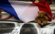 A picture taken on December 2, 2015 in Paris shows a cuddly toy and a French flag at a makeshift memorial in front of the statue of the Republique in tribute to the victims of November 13 terror attacks in Paris.