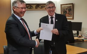 Trade Minister David Parker receiving a note from the Australian High Commissioner Ewen McDonald confirming Australia's ratification.