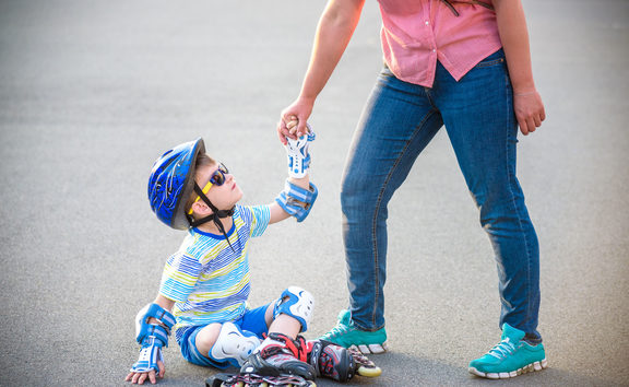A photo of a Preschooler falling over while rollerblading with mother in the park.