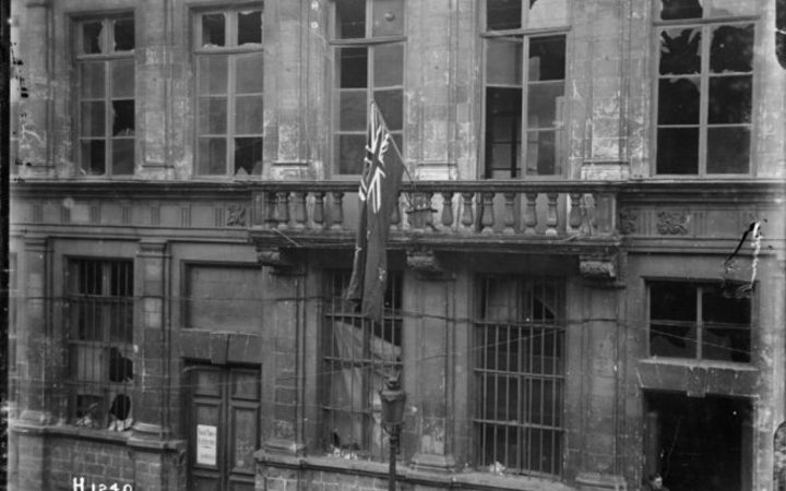 New Zealand flag handing outside Le Quesnoy's war-damaged town hall in 1918