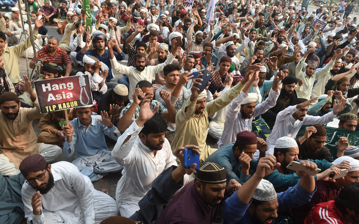 Crowds chant slogans during a protest against the court decision to overturn the conviction of Christian woman Asia Bibi