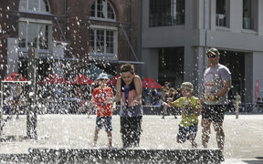 Summer in Wellington, a boy is splashed by the people jumping into the harbour.