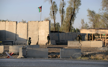 Afghan security personel stand guard near the airport complex in Kandahar on December 9, 2015.