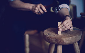 Juliet Arnott knocking in an oak wedge into a greewnwood stool made from ash elm from Hagley Park. Image by Justyn Rebecca Denney