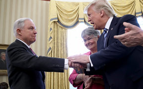Jeff Sessions shakes hands with US President Donald Trump.
