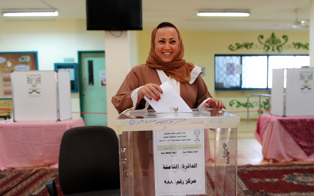 A Saudi woman arrives at a polling station to vote for the municipal elections
