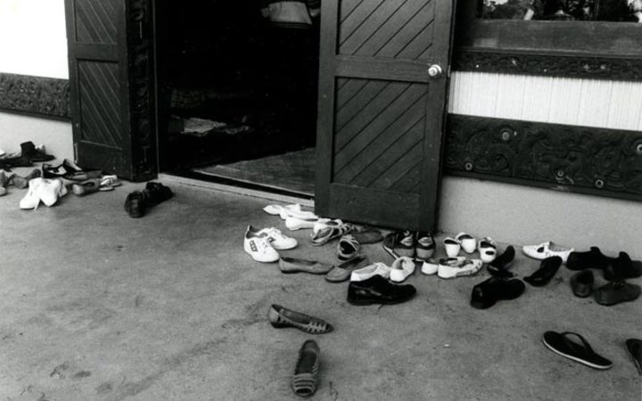 Shoes outside a wharenui are a common sight. Photograph by Gil Hanly, source Te Ara: https://teara.govt.nz/en/photograph/41374/shoes-at-the-door-of-the-wharenui