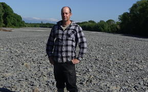 Ongaonga farmer Alistair Setter stands in the middle of the dry Waipawa River bed.