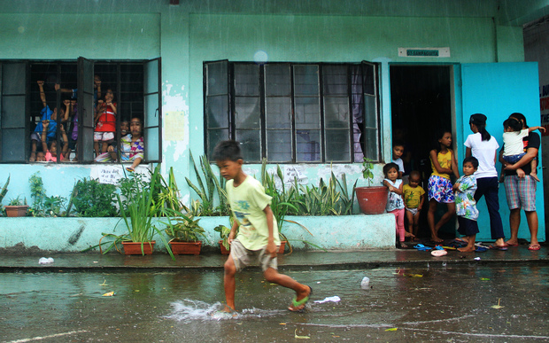 A young evacuee wades through flooded school grounds while others look on from a school building being used as an evacuation center in the city of Legaspi in Albay province, south of Manila on December 14, 2015,