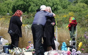 Sonya Rockhouse receives a hug from Bernie Monk at a memorial site for 29 men near the turnoff to the Pike River Mine. 