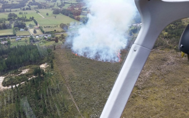 Ten homes were evacuated as fire raged through dry scrub near a pine forest just west of Ngawha in Northland on 13 December 2015.
