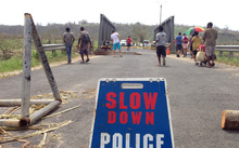 Police block access to a bridge that was badly damaged by Cyclone Pam, near the Vanuatu capital of Port Vila.