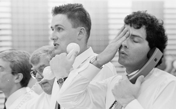 Stuart Beadle (right), sharemarket operator for Francis, Alison, Symes and Co, and colleague Grant Taylor show the stress of dealing with the fall in stock prices, 25 October 1987.