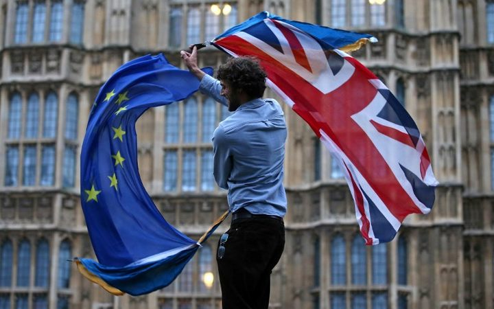 File photo taken on June 28, 2016. A  man waves both a Union flag and a European Union (EU) flag outside The Houses of Parliament at an anti-Brexit protest in central London.