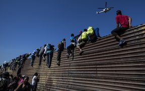 A group of Central American migrants climb a metal barrier on the Mexico-US border.