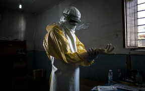 A health worker puts on protective equipment before entering the red zone of a MSF (Doctors Without Borders) supported Ebola Treatment Centre.