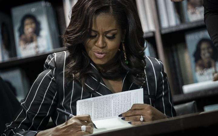 Former U.S. First Lady Michelle Obama signs copies of her new book 'Becoming' during a book signing event in New York City. The memoir has sold more than 2 million copies in all formats in North America during its first 15 days on the market.