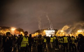 """Yellow vests"" demonstrators wave Breton and French flags in front of the Arc de Triomphe, which was completely destroyed inside."