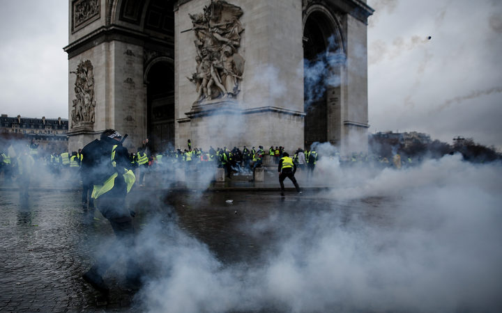Demonstrators clash with riot police at the Arc de Triomphe during a protest of Yellow vests (Gilets jaunes) against rising oil prices and living costs.