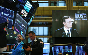 Traders work on the floor of the New York Stock Exchange (NYSE) as a picture of former President George H.W. Bush appears on a screen.