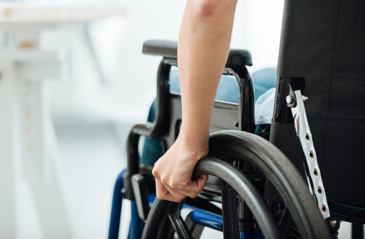 Woman in wheelchair next to an office desk, hand close up, unrecognizable person