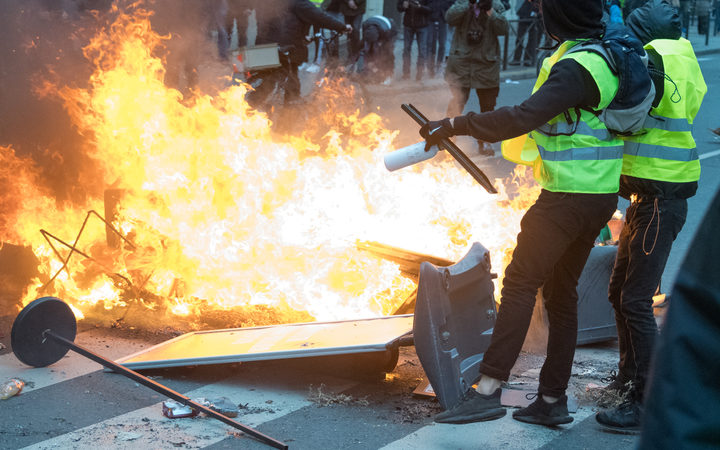 Two Gilet Jaune near a barricade on fire near the Gare Saint-Lazare on December 8, 2018 in Paris, France.